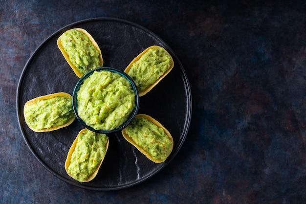 Patatine fritte con guacamole su una banda nera. salsa guacamole messicana con patatine su sfondo scuro. concetto di cibo messicano a forma di fiore. copia spazio. vista dall'alto