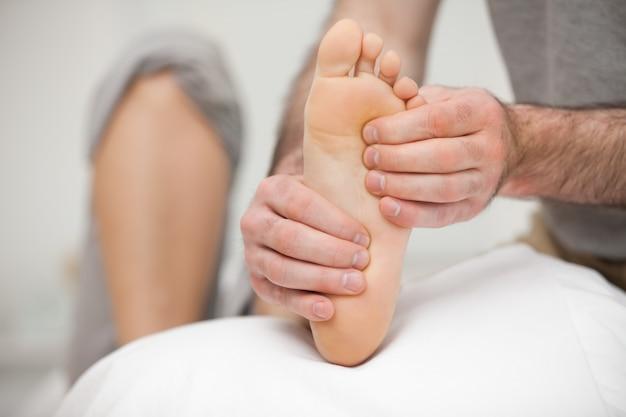 Podologo che palpa la pianta del piede di un paziente