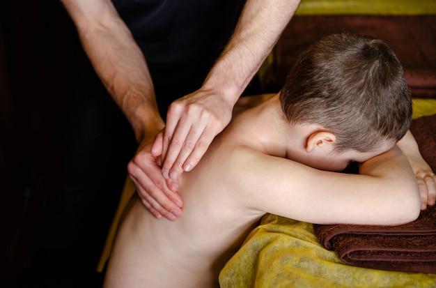 Chiropratica, osteopatia, manipolazione dorsale. terapista che fa un trattamento curativo sulla schiena dell'uomo. medicina alternativa, concetto di sollievo dal dolore. un adolescente riceve un massaggio medico alla schiena e al collo