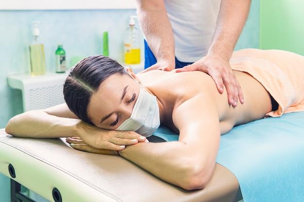 Massaggio di terapia termale di riflessologia chiropratica in maschera facciale. un massaggiatore maschio fa un massaggio a una giovane e bellissima ragazza.