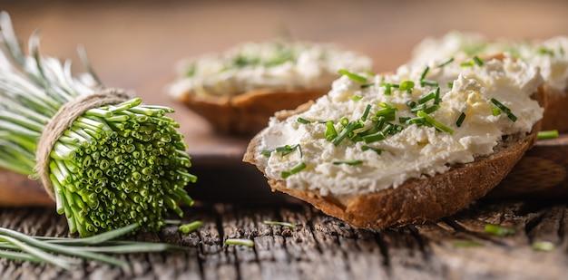 Crema di formaggio all'erba cipollina spalmata su fette di pane accanto a un mazzetto di erba cipollina appena tagliata su un legno rustico e tagliere.