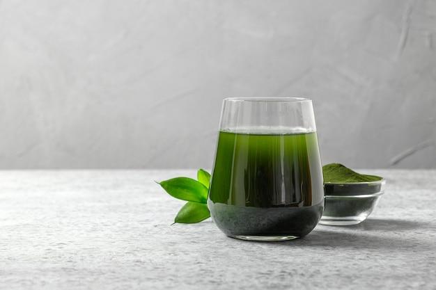 Clorella bevanda disintossicante sana in vetro e polvere in una ciotola su uno spazio grigio