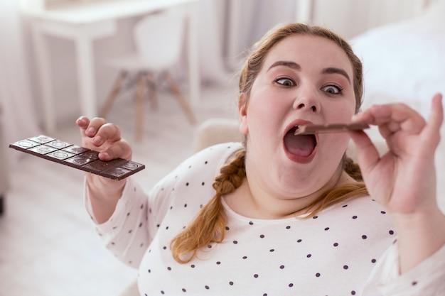 Dipendenza dal cioccolato. donna grassoccia pazza che mangia cioccolato inarrestabilmente