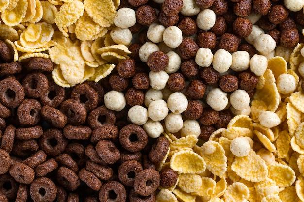 Cioccolato, palline, anelli e corn flakes gialli per una sana colazione a base di cereali
