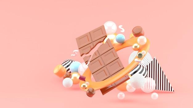 Chocolate bar tra le palline colorate sullo spazio rosa