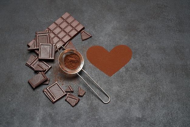 Barretta di cioccolato e cacao in polvere sul tavolo di cemento scuro