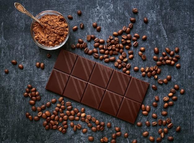 Barretta di cioccolato, cacao in polvere e chicchi di caffè fritti freschi