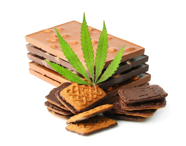 Primo piano di barrette e biscotti di cioccolato con foglia di canapa. biscotti da dessert al cioccolato e marijuana con cannabis cbd