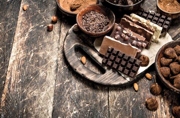Tavolette di cioccolato con tartufo e cacao in polvere. su uno sfondo di legno.