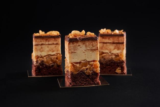 Pezzi di torta di mousse di biscotti al cioccolato isolati sul nero.