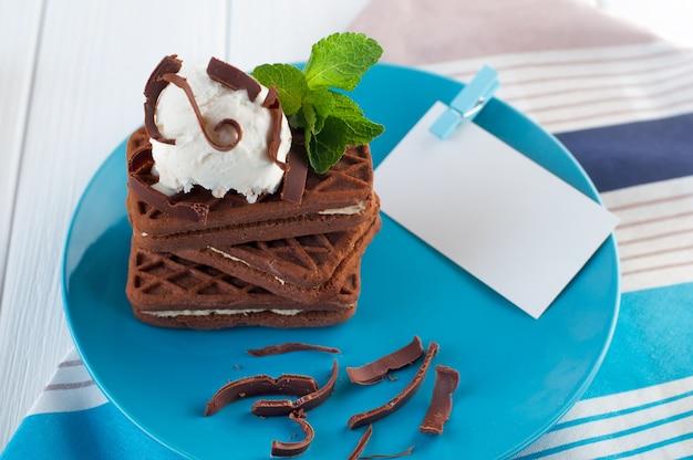 Biscotti al cioccolato ricoperti di gelato e menta accanto al cartoncino