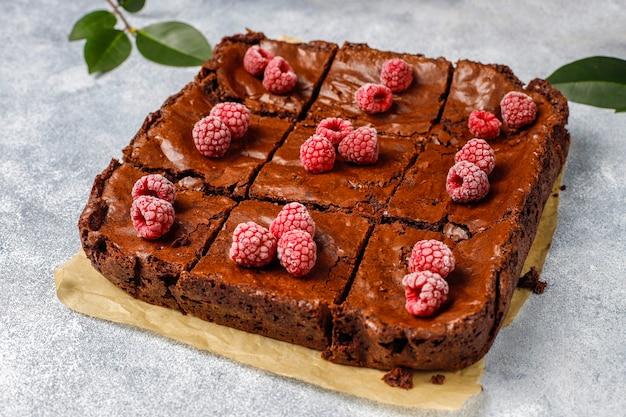 Fette del dessert del dolce del brownie del cioccolato con i lamponi e le spezie, vista superiore