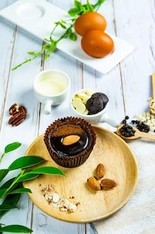 Torta brownie al cioccolato in bicchieri di carta decorata con componenti per fare torte appoggiate su legno