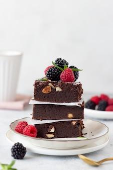 Pezzi quadrati di brownie al cioccolato con frutti di bosco
