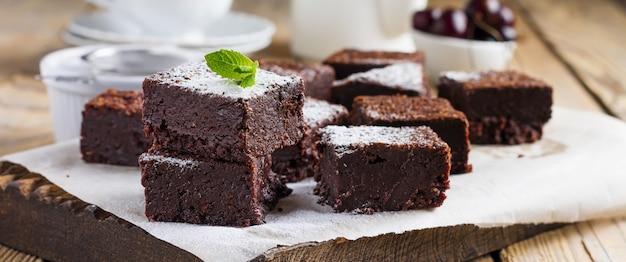 Brownies al cioccolato con zucchero a velo e ciliegie su uno sfondo di legno scuro. messa a fuoco selettiva.