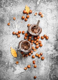 Burro al cioccolato con nocciole. su fondo rustico.