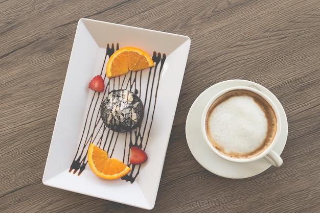 Torta al cioccolato o torta di lava al cioccolato con frutta fresca e caffè su fondo di legno