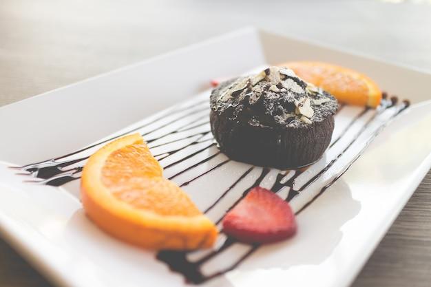 Torta al cioccolato o torta al cioccolato di lava con frutta fresca e caffè