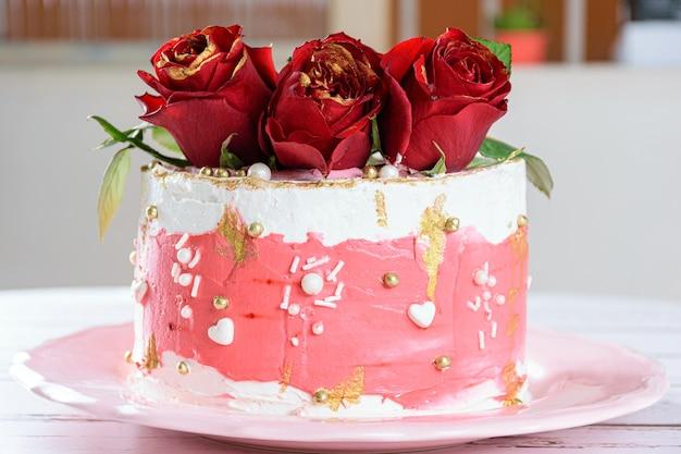 Torta al cioccolato ricoperta di crema al burro di meringa svizzera, con tre fiori rossi in cima (vista laterale).