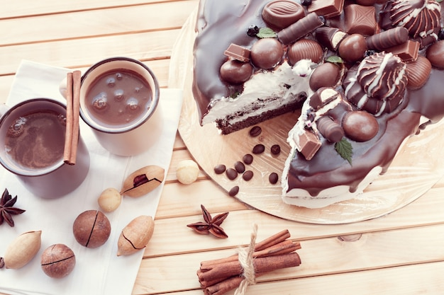Torta al cioccolato decorata con cioccolatini con noci di macadamia e due tazze di caffè