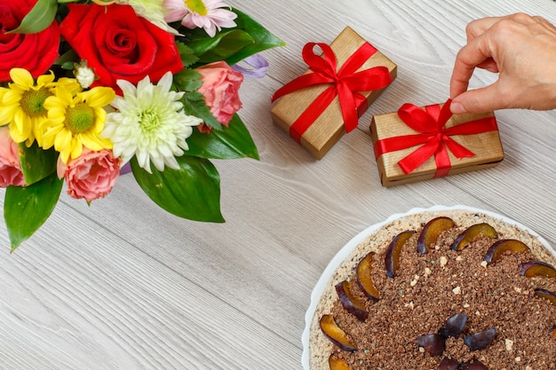 Torta al cioccolato decorata con prugne, un mazzo di fiori e scatole regalo sulle tavole di legno grigie. vista dall'alto.