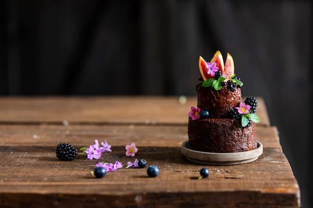 Torta al cioccolato con mora e fichi comuni sul tavolo di legno