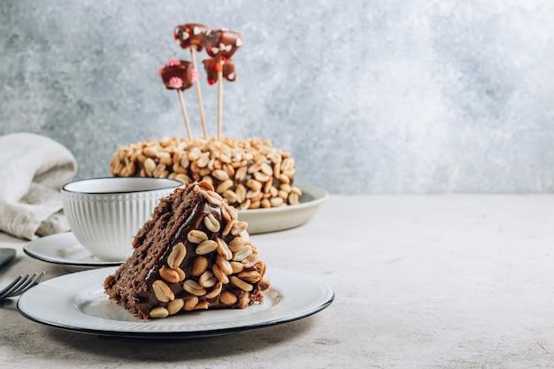 Torta al cioccolato con crema al caramello e arachidi su sfondo concreto. decorato con cuori di marshmallow al cioccolato. messa a fuoco selettiva