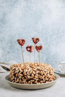Torta al cioccolato con crema al caramello e arachidi su sfondo concreto. decorato con cuori di marshmallow al cioccolato