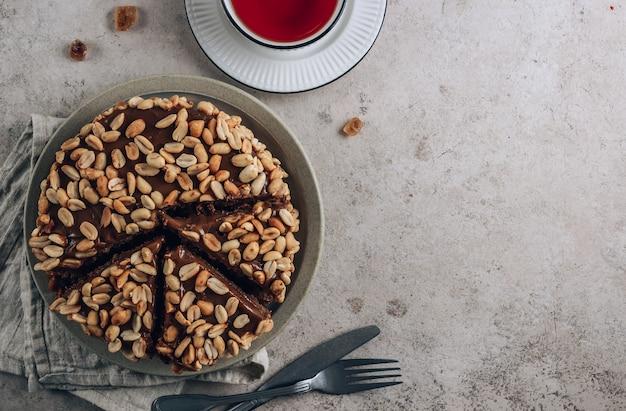 Torta al cioccolato con crema al caramello e arachidi su sfondo concreto.