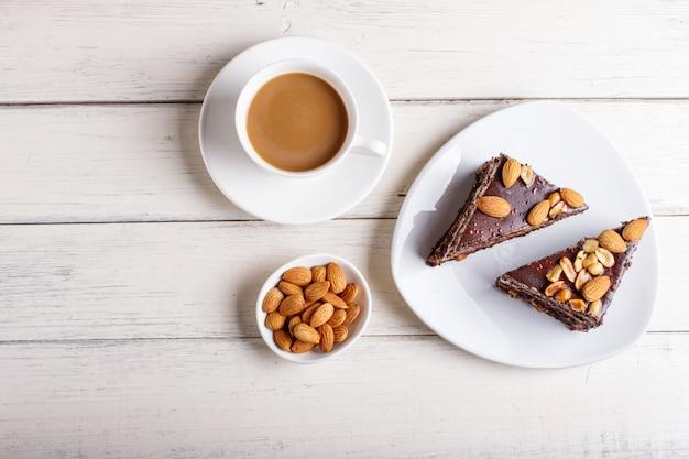 Torta al cioccolato con caramello, arachidi e mandorle su un fondo di legno bianco.
