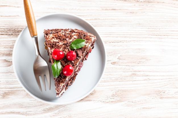 Torta al cioccolato con ciliegia su fondo in legno chiaro