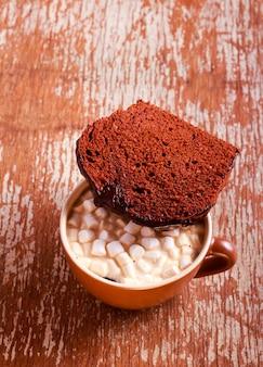Torta al cioccolato con glassa al cioccolato e bevanda con marshmallow