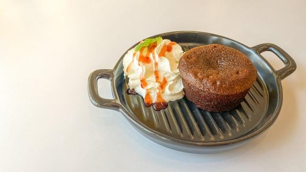 Torta al cioccolato con crema nella piccola padella sul tavolo bianco
