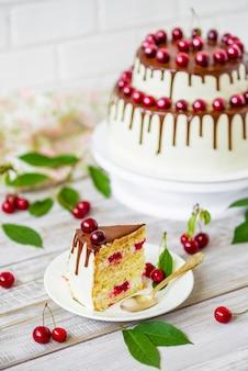 Torta al cioccolato con ciliegie organiche fresche su fondo di legno rustico chiaro.