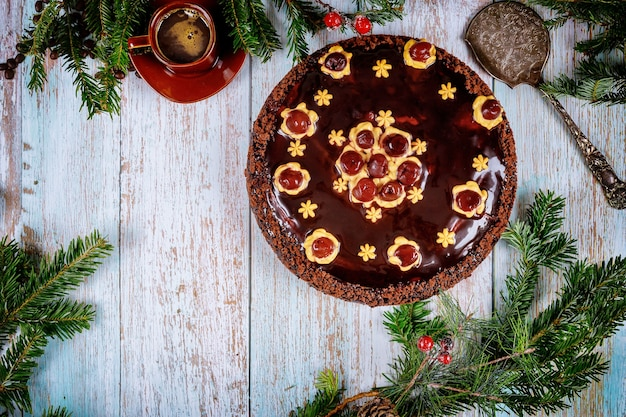 Torta al cioccolato con rami di abete rosso su legno. concetto di natale o capodanno.