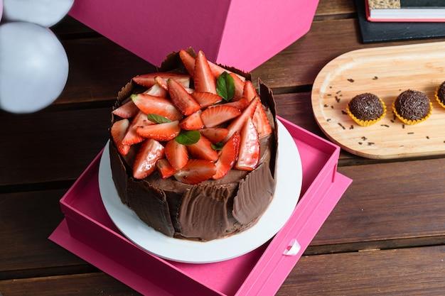 Torta al cioccolato con fragole, foglie di basilico, marmellata di more e piatti di cioccolato intorno. accanto a palloncini e brigadiere.