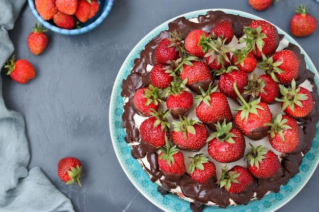 Torta al cioccolato con fragole e panna situata su uno sfondo scuro, vista dall'alto, foto orizzontale