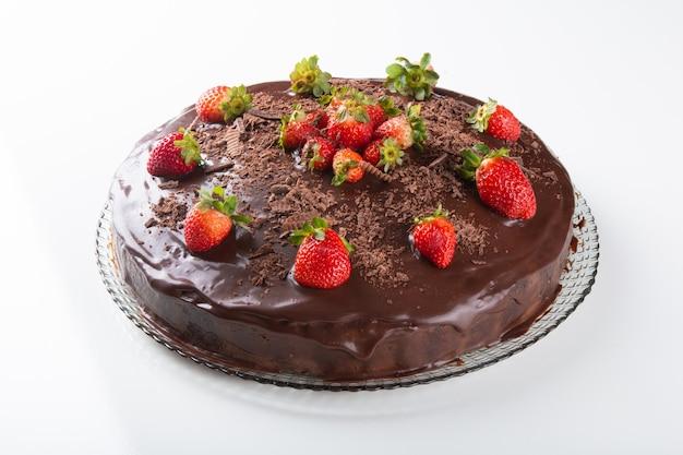 Torta al cioccolato con fragole isolato su superficie bianca.