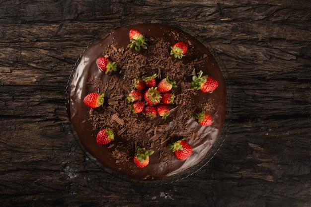 Torta al cioccolato con fragola isolata sulla vista dall'alto della superficie di legno.