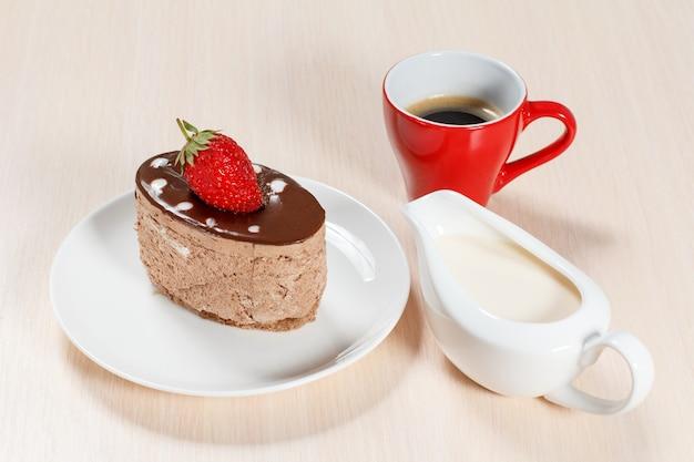 Torta al cioccolato con fragole sul piatto bianco, una tazza di caffè e una salsiera con crema su un tavolo di legno