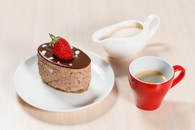 Torta al cioccolato con fragole sul piatto bianco, una tazza di caffè e una salsiera con latte su un tavolo di legno
