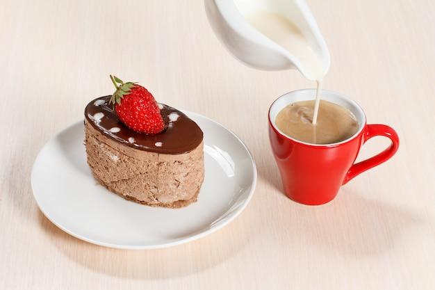 Torta al cioccolato con fragole sul piatto bianco, una tazza di caffè in cui viene aggiunto il latte da una salsiera