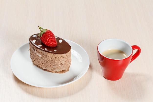 Torta al cioccolato con fragole sul piatto bianco e una tazza di caffè su un tavolo di legno