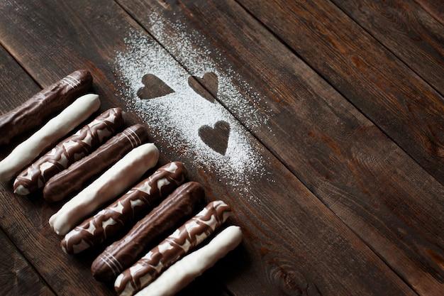 Torte al cioccolato con forme di cuore di zucchero in polvere sulla scrivania
