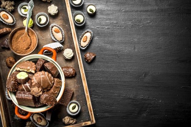 Caramelle di cioccolato in una ciotola. sulla lavagna nera.
