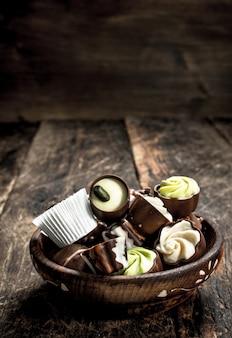 Caramelle di cioccolato in una ciotola. su uno sfondo di legno.