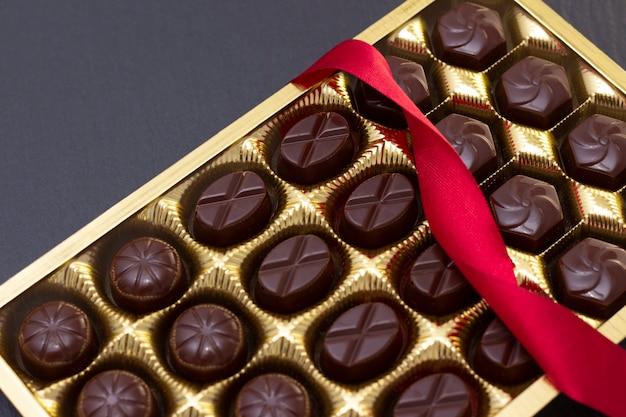 Caramelle di cioccolato in una scatola con un fiocco rosso su una superficie nera. foto scura, umore.
