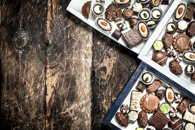 Caramelle di cioccolato in scatole. su uno sfondo di legno.
