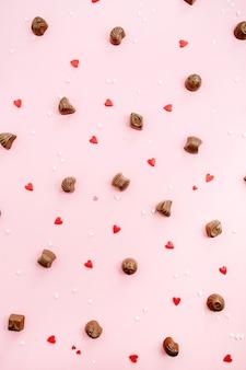 Caramelle al cioccolato e si riscalda su sfondo rosa pallido. disposizione piatta, vista dall'alto