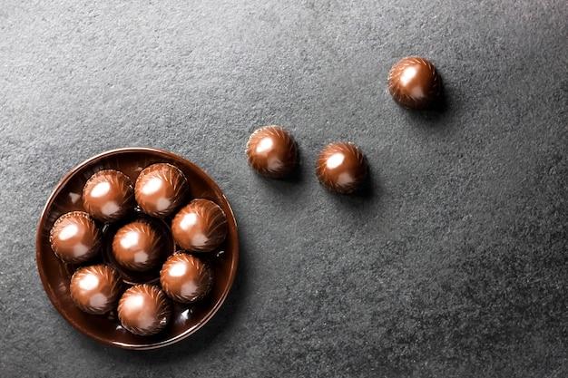 Caramelle di cioccolato su una zolla sul nero con lo spazio della copia